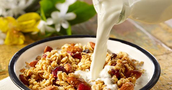 Reduced Fat White milk from Promised Land Dairy poured in granola cereal